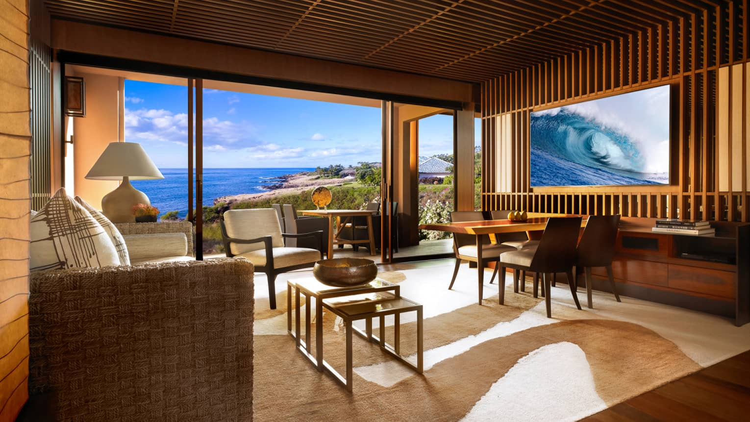 Four Seasons Ocean-View Suite spacious living room with teak-panel walls, sofa, TV displaying waves