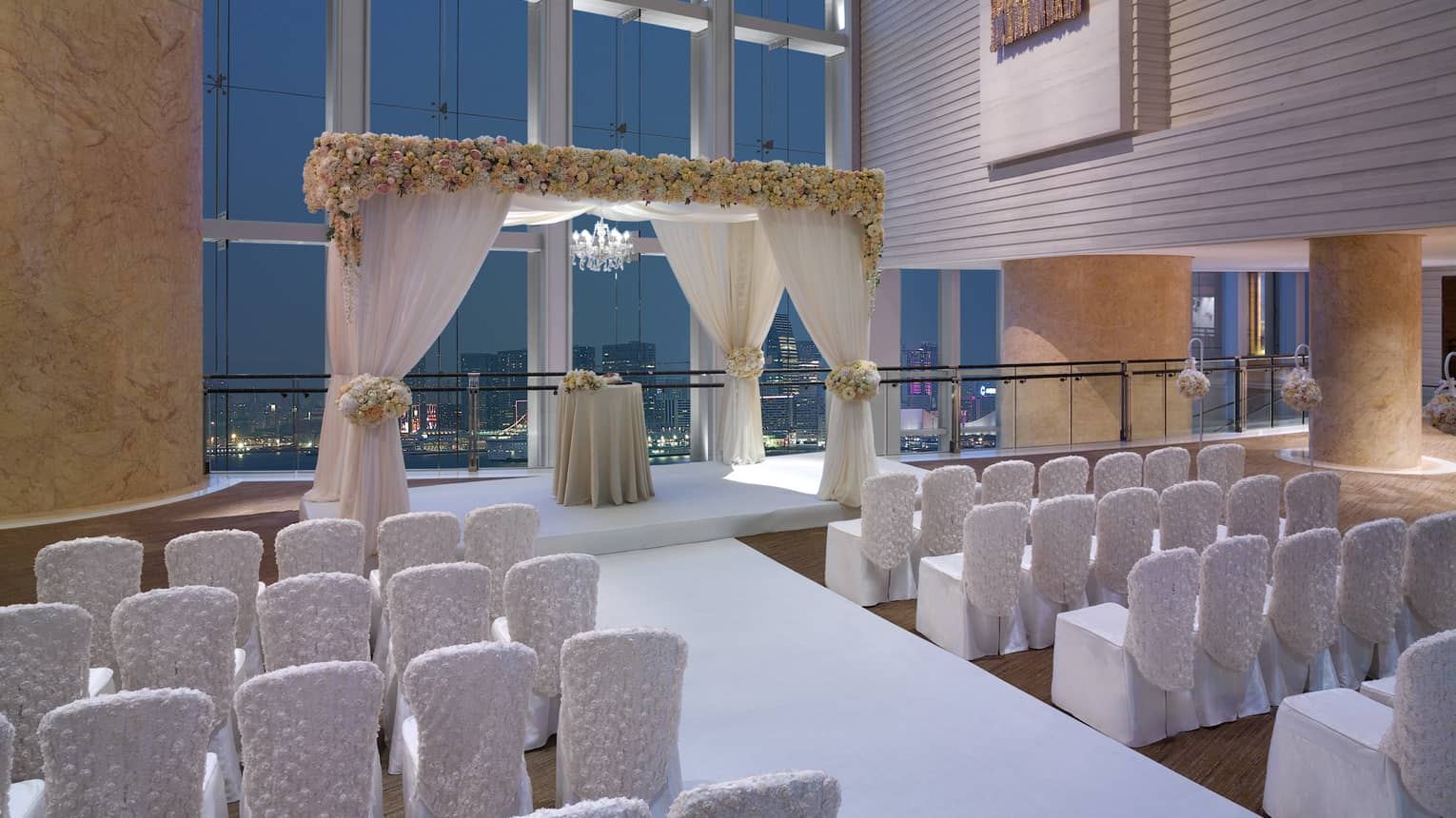 Rows of white chairs face wedding altar under tall loft windows