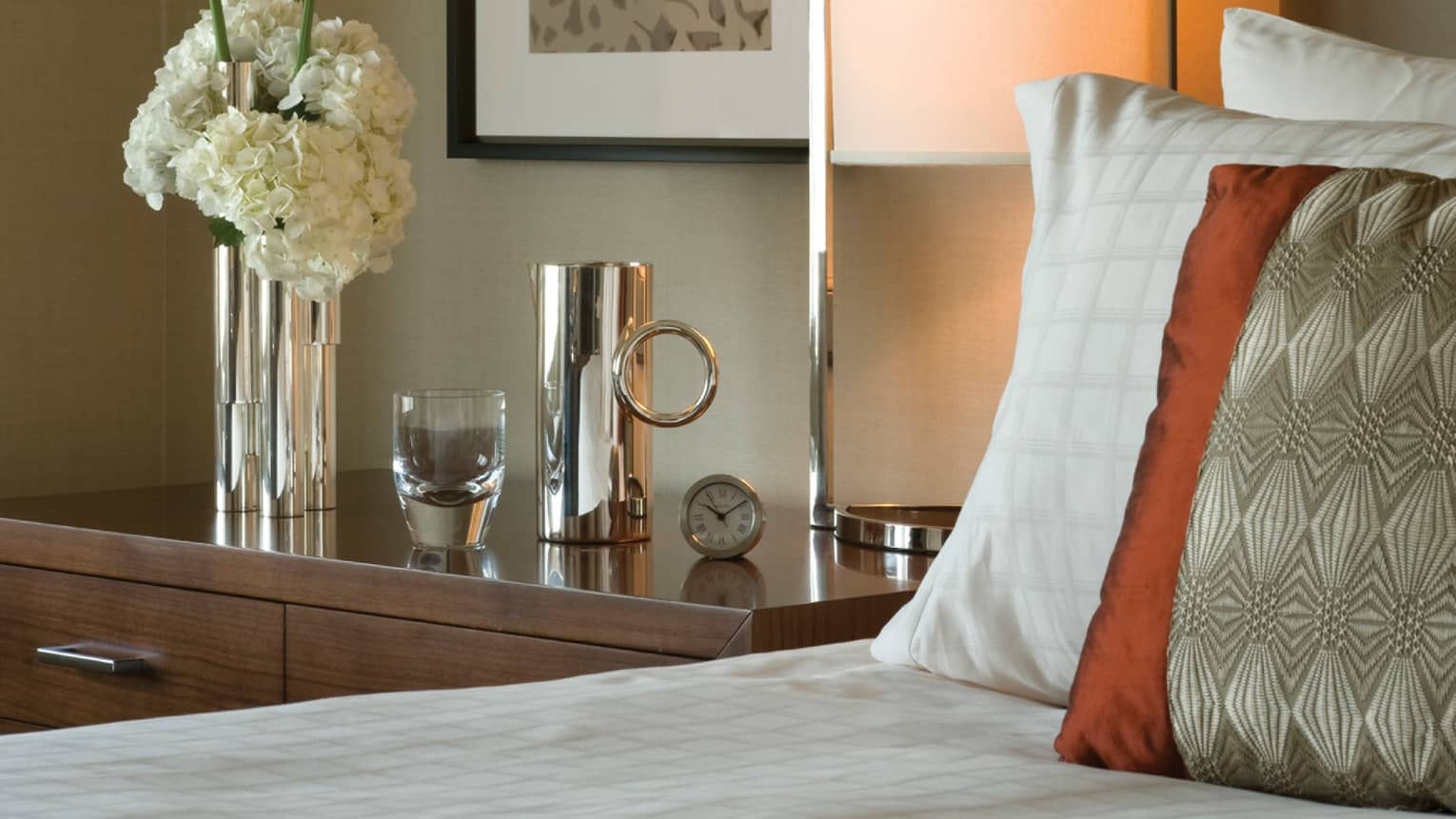 Premium Room close-up of bedside table with clock, silver vase with fresh white flowers, glass, canister, silk pillow on bed