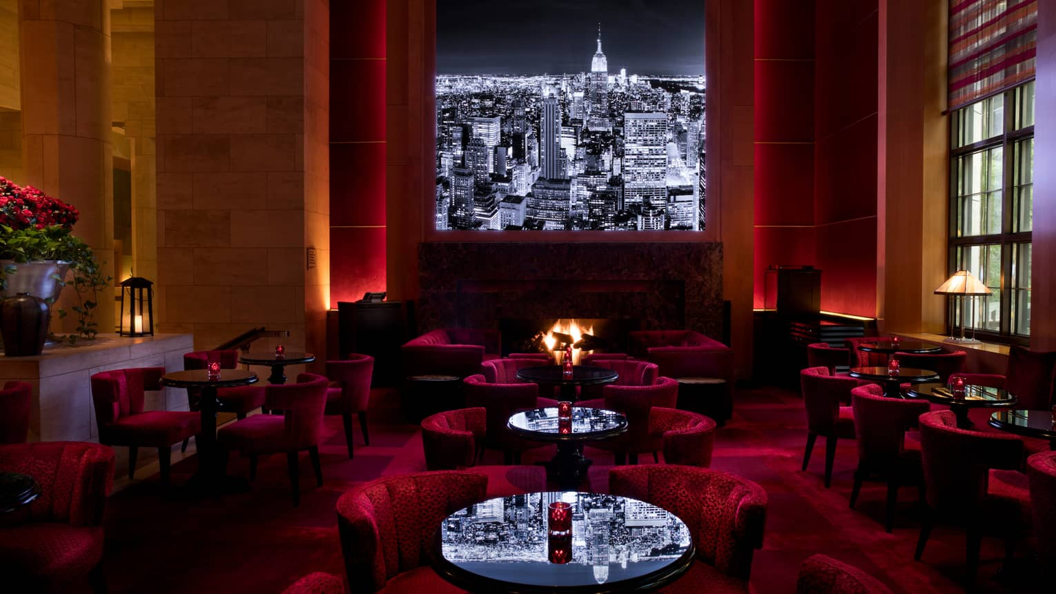 Black-and-white city skyline image above red velvet lounge chairs, cocktail tables