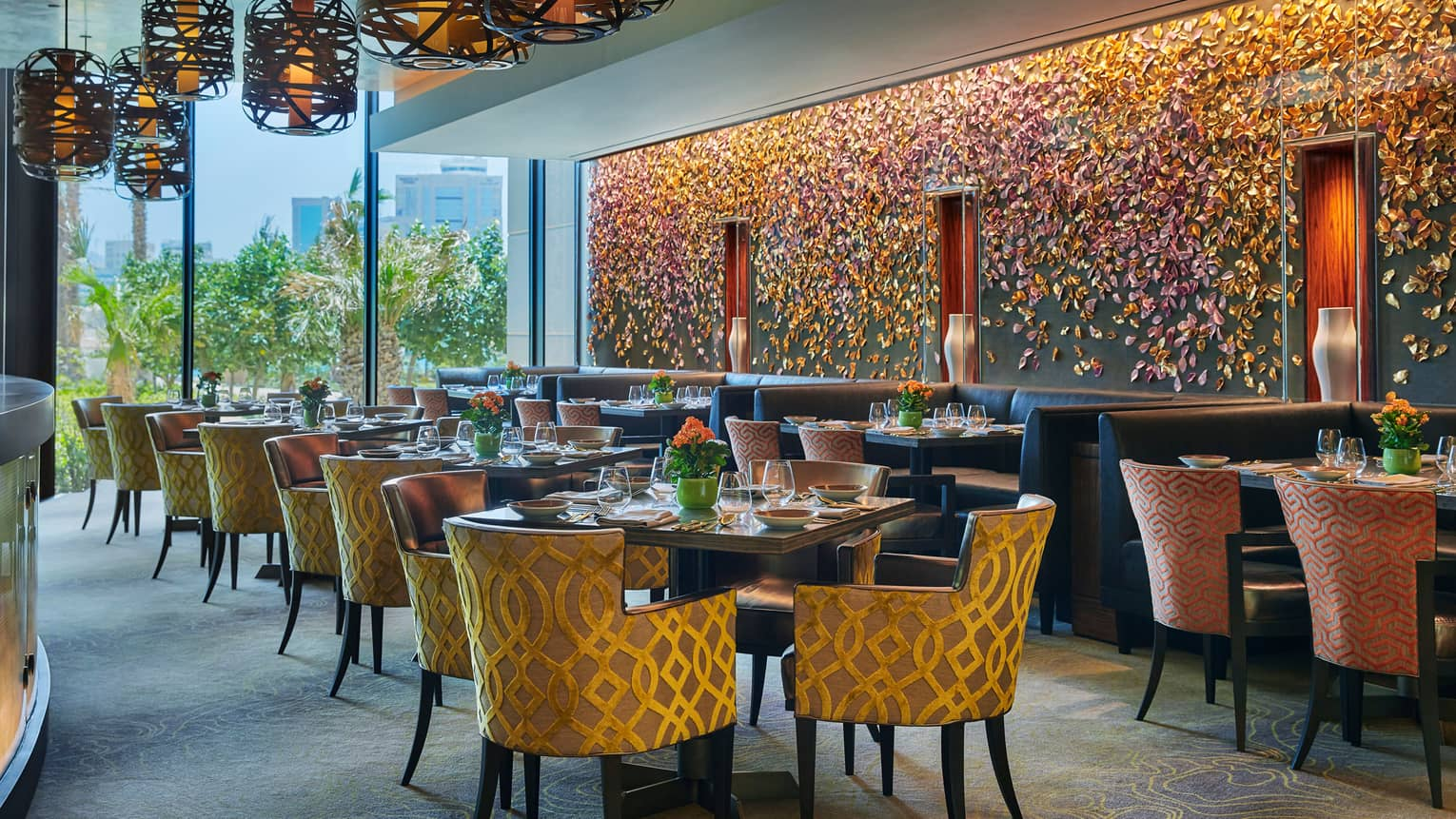Bahrain Bay Kitchen elegant indoor dining room with chairs with gold details, formal dining tables, flower-petal mural