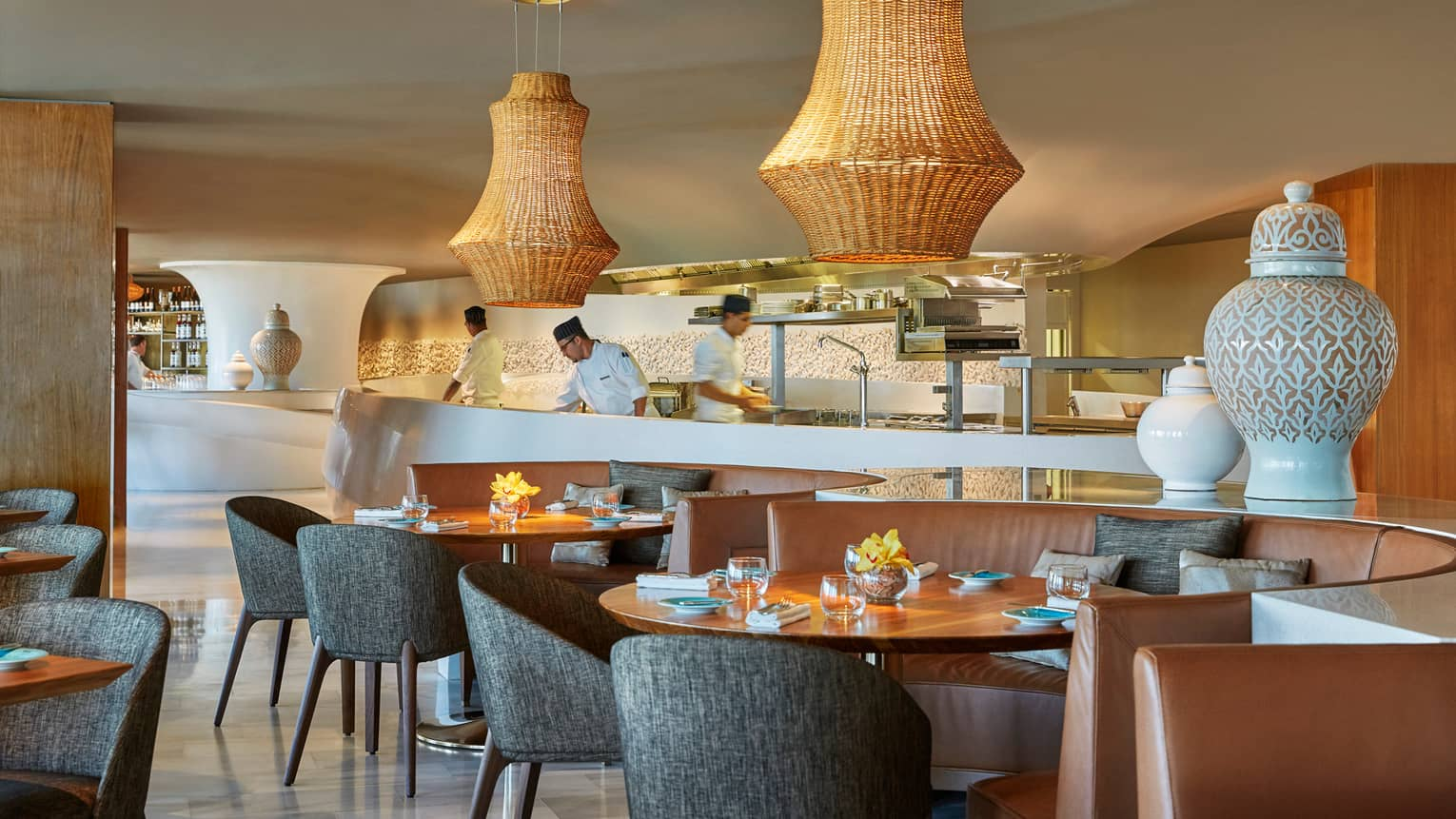 Large wicker lamps hang over mid-century style dining tables and chairs at Blue restaurant, chefs work in background