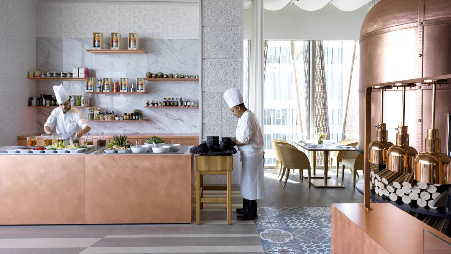Chefs in white uniforms, hats prepare buffet counter in sunny dining room