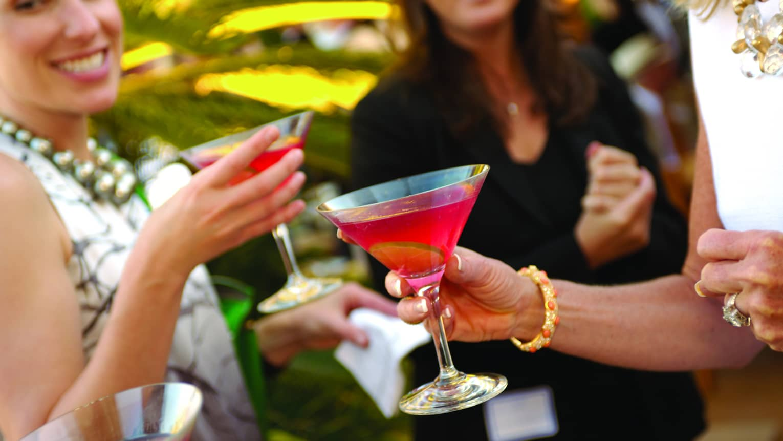 Group of smiling women holding colourful cocktails in sunny garden