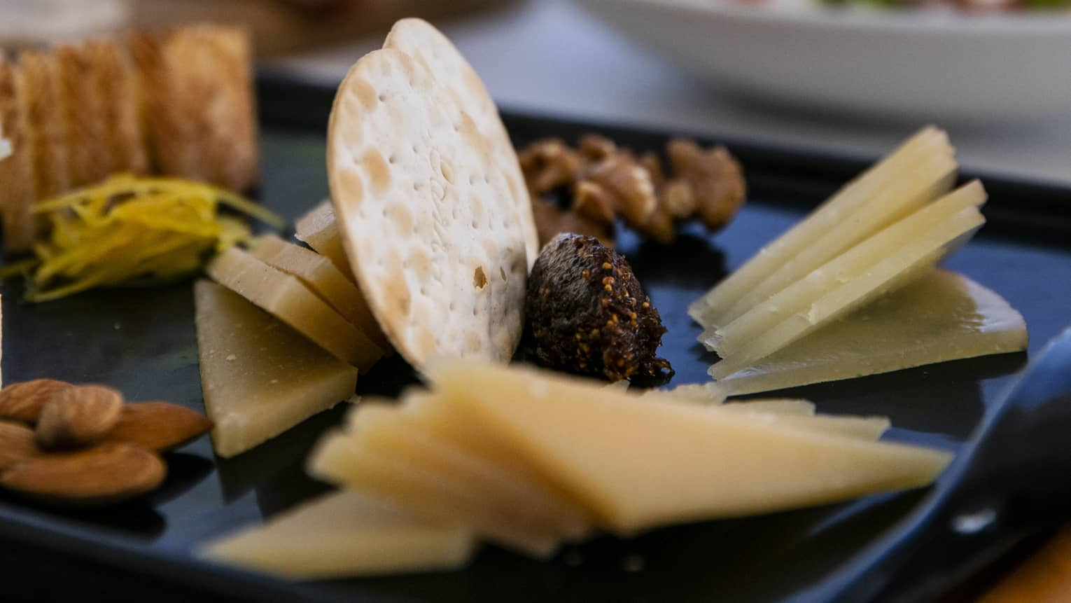 A charteurtie board with cheese, crackers, almonds and raisins