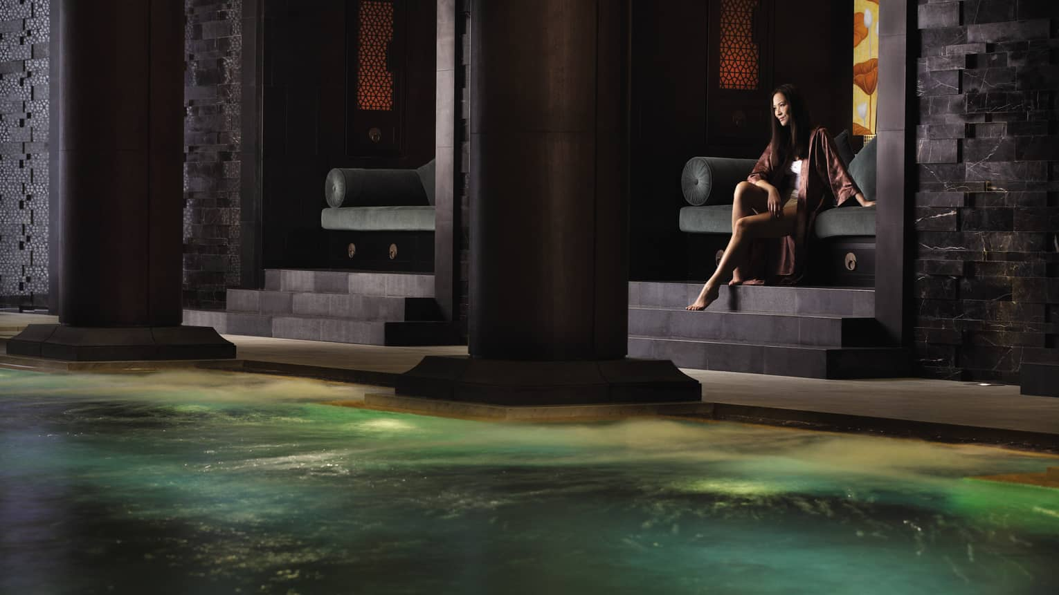Woman in robe sits on dark velvet chair over slate steps to large black pillar, spa pool