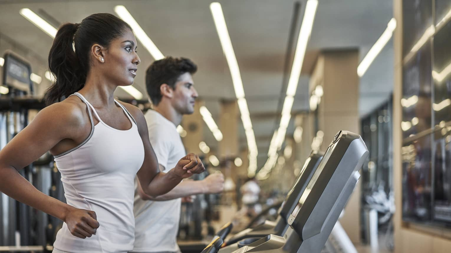 A woman and man, both dressed in all white run on indoor treadmills side by side at the four seasons philadelphia fitness centre.