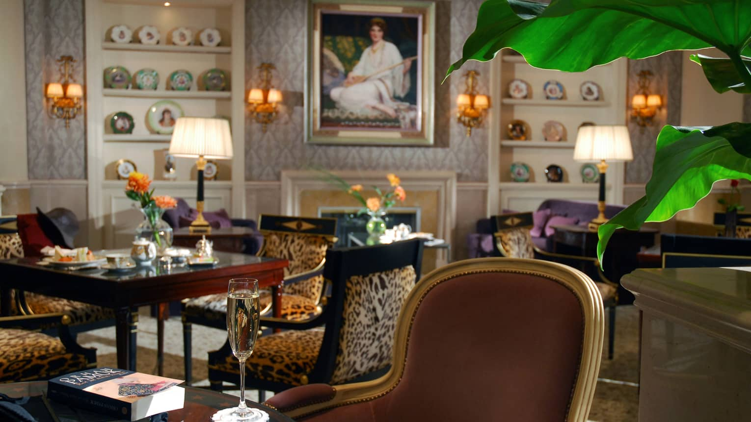 Lobby Lounge with leopard print dining chairs, Champagne on tables, large paintings and shelves with decorative plates