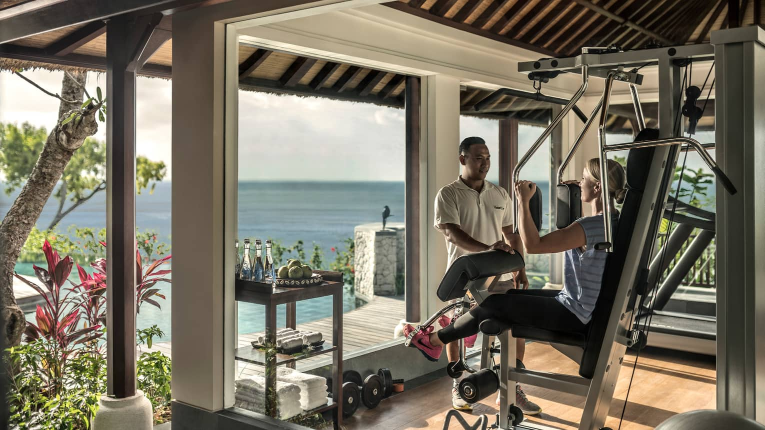 Imperial Villa private gym, trainer assists women on weights machine by window with ocean view