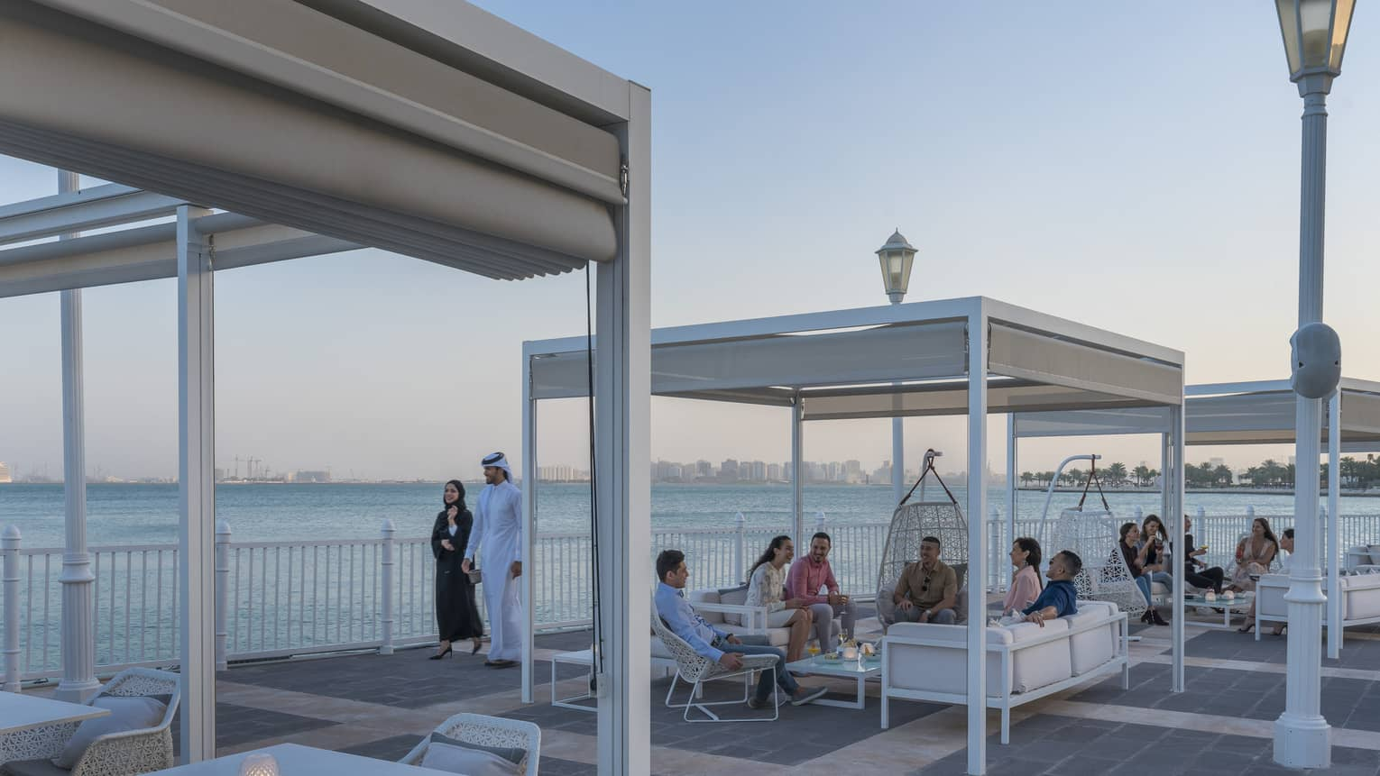 People mingle at outdoor lounge The Pier at Four Seasons Doha, overlooking the sea