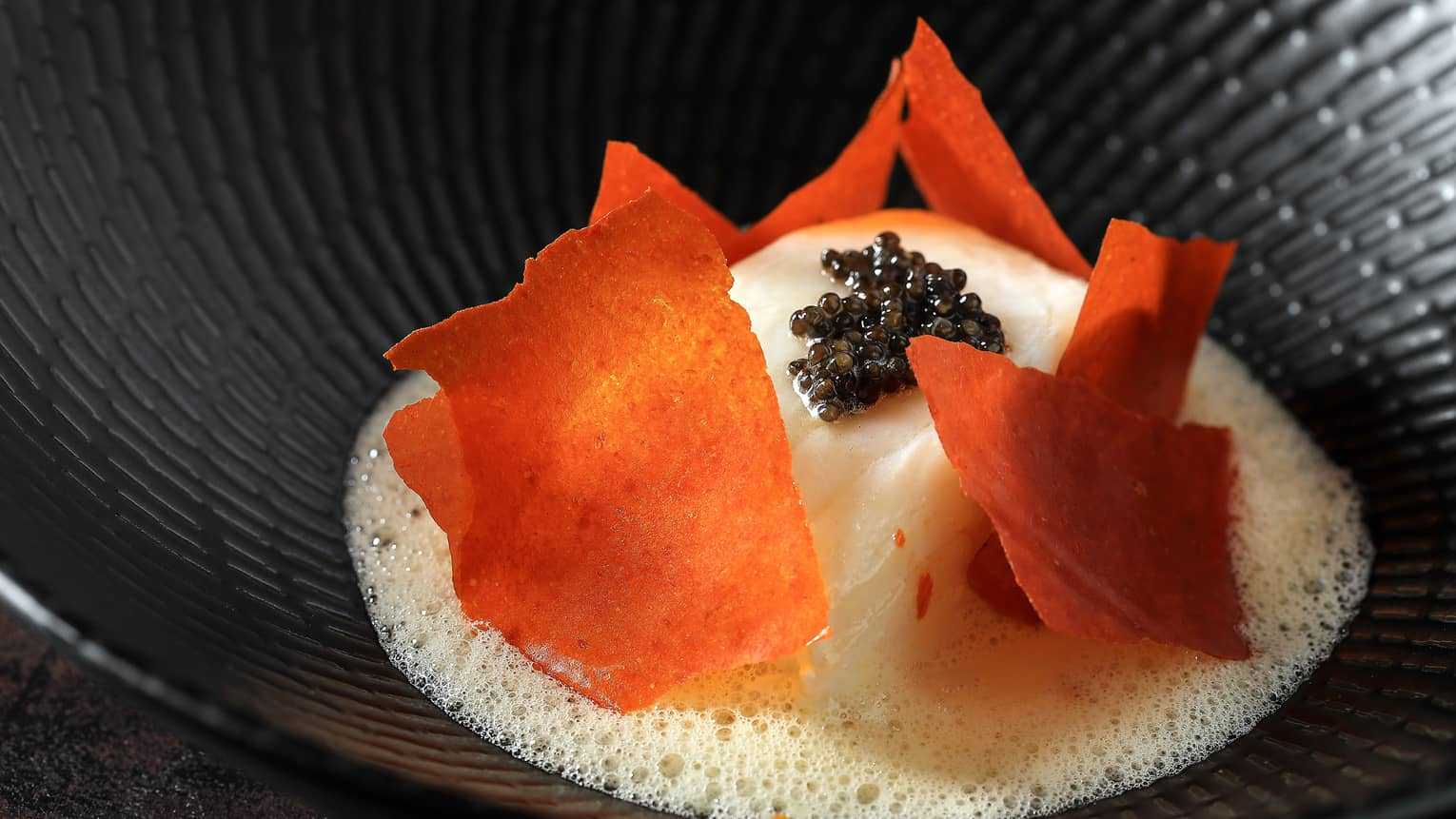 Alaskan Black Cod white fish filet topped with orange dried pepper, black caviar