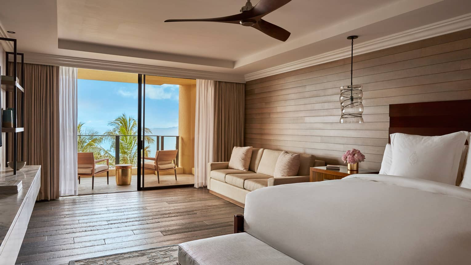 Elite Suite bedroom with doors out to a private terrace with view of the ocean