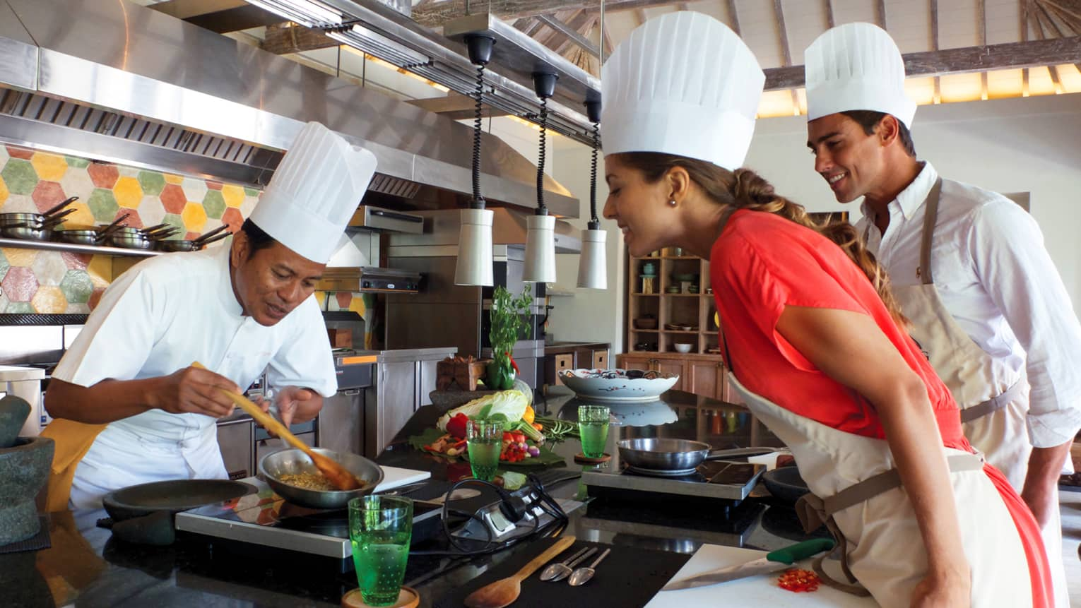 Chef in white hat, uniform stirs food in pan as woman and man in chef's hat, apron watch, smile