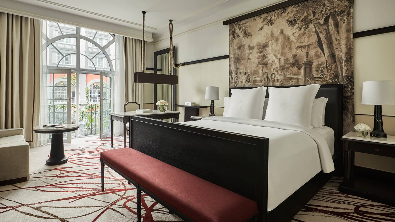 Premier Room bed under print headboard, red bench at foot, sunny arched balcony glass doors