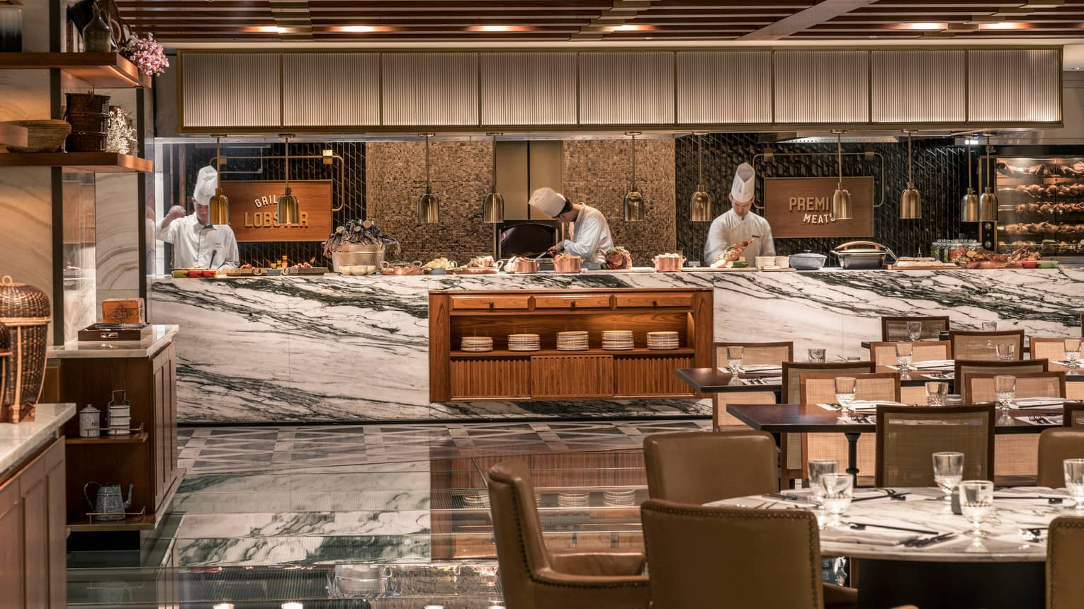 Chefs work behind white marble counter with copper pots at The Market Kitchen
