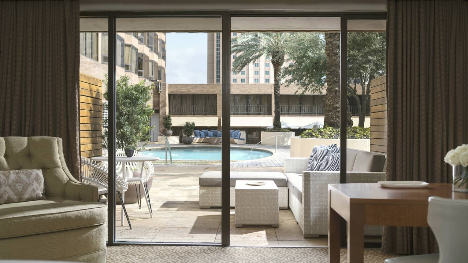 Sliding doors of the king-sized poolside room, looking out at patio and swimming pool