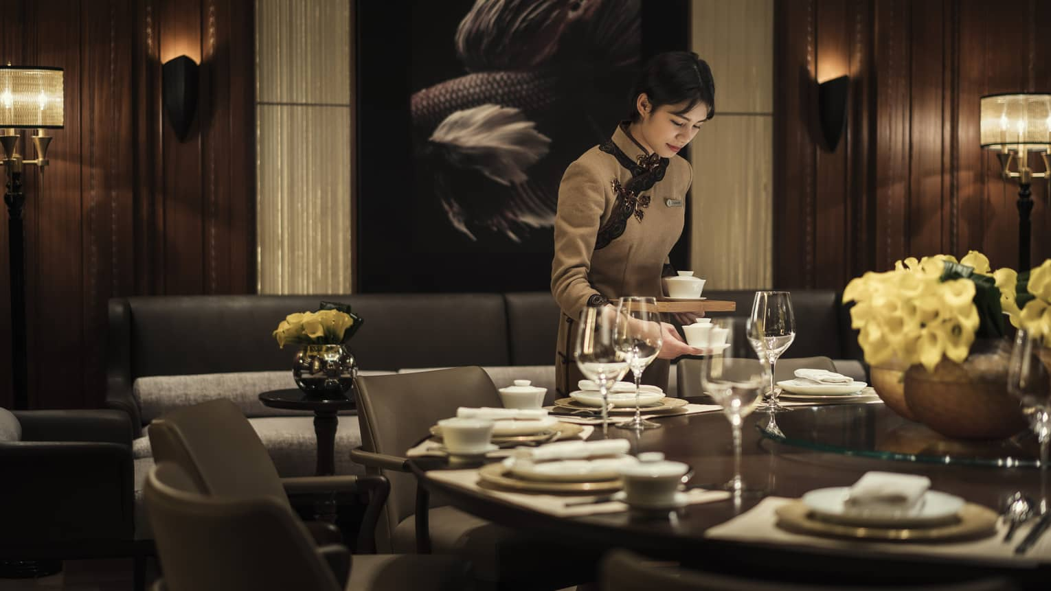 Hotel staff sets dishes on restaurant table
