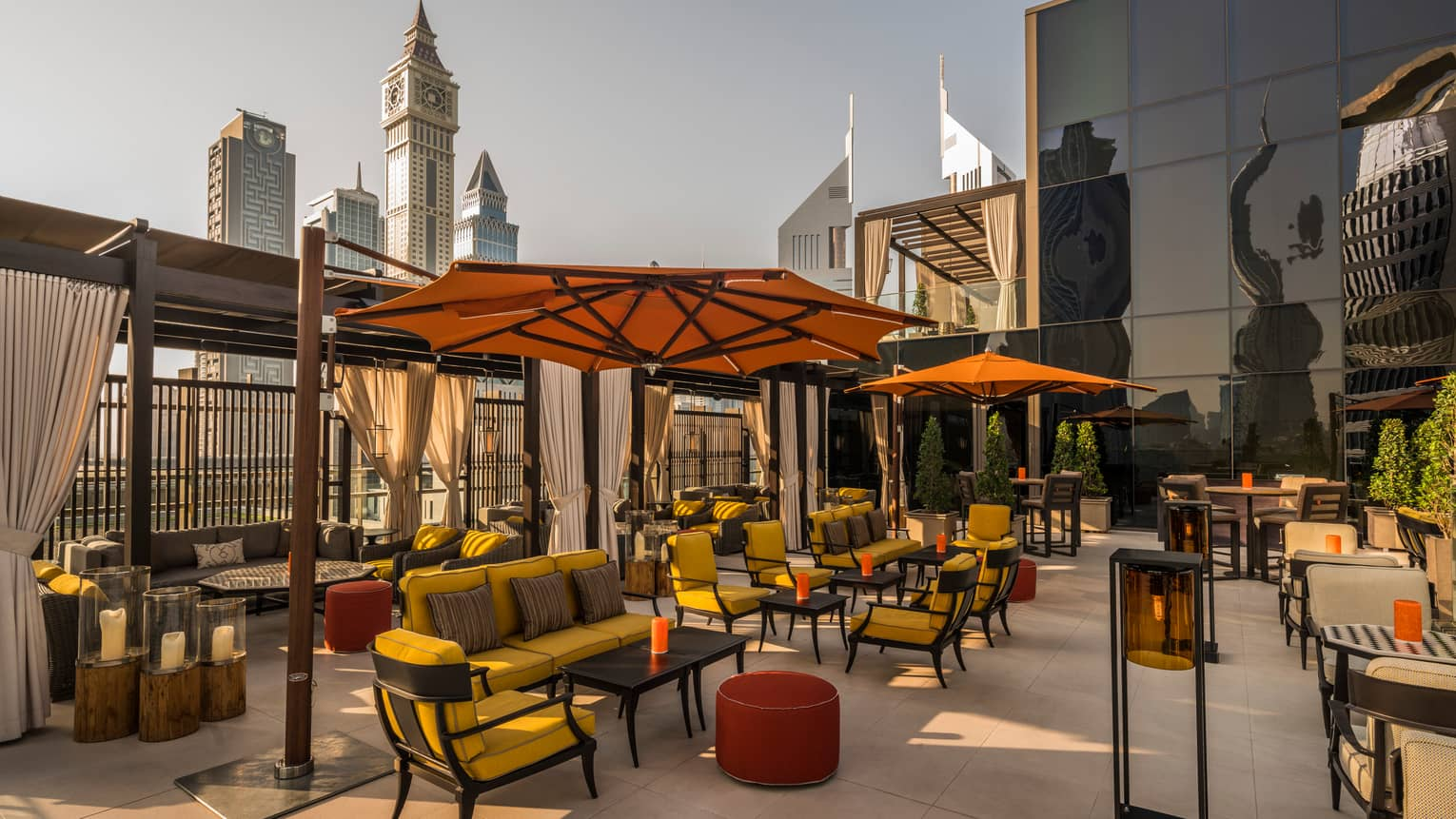 Rooftop patio with plush yellow patio furniture, large orange umbrellas, wood pergolas, city skyline in background