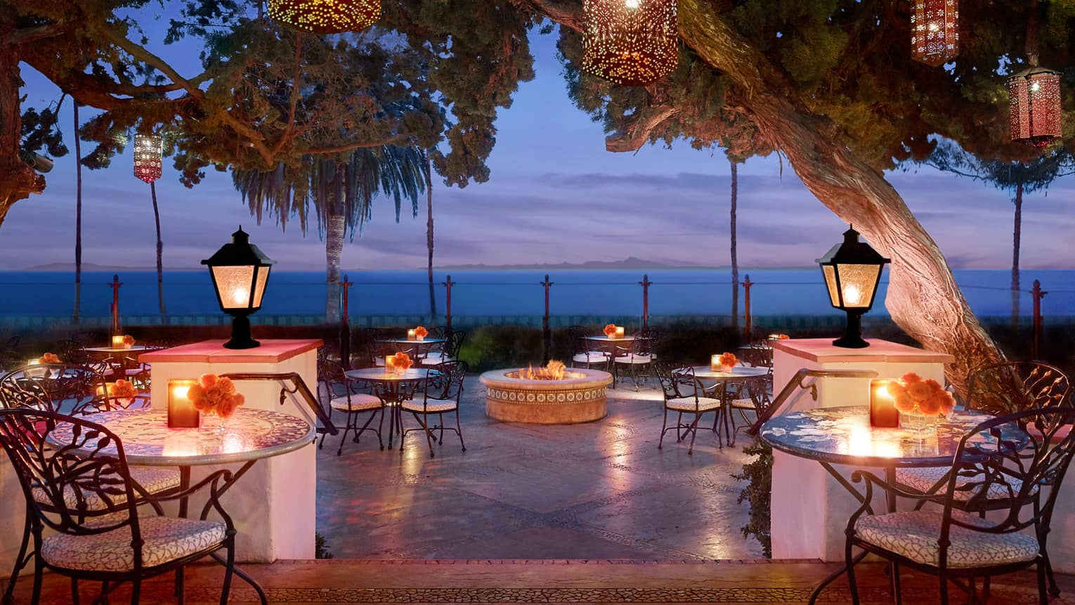 Bella Vista patio at dusk with candle-lit tables under lanterns on posts, hanging from trees