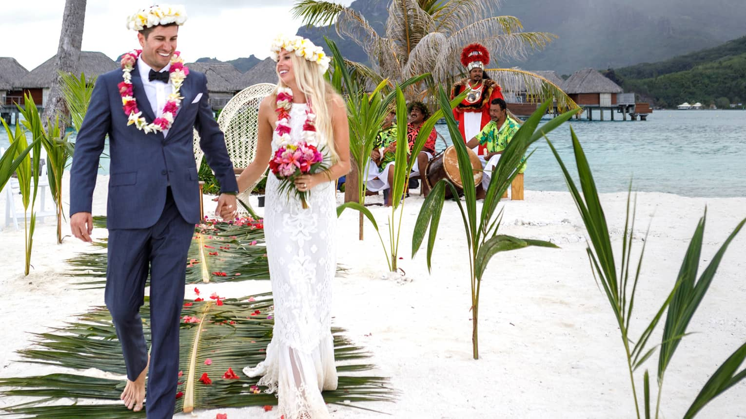 Bride and groom wearing floral crowns walk down aisle on white sand beach with palms