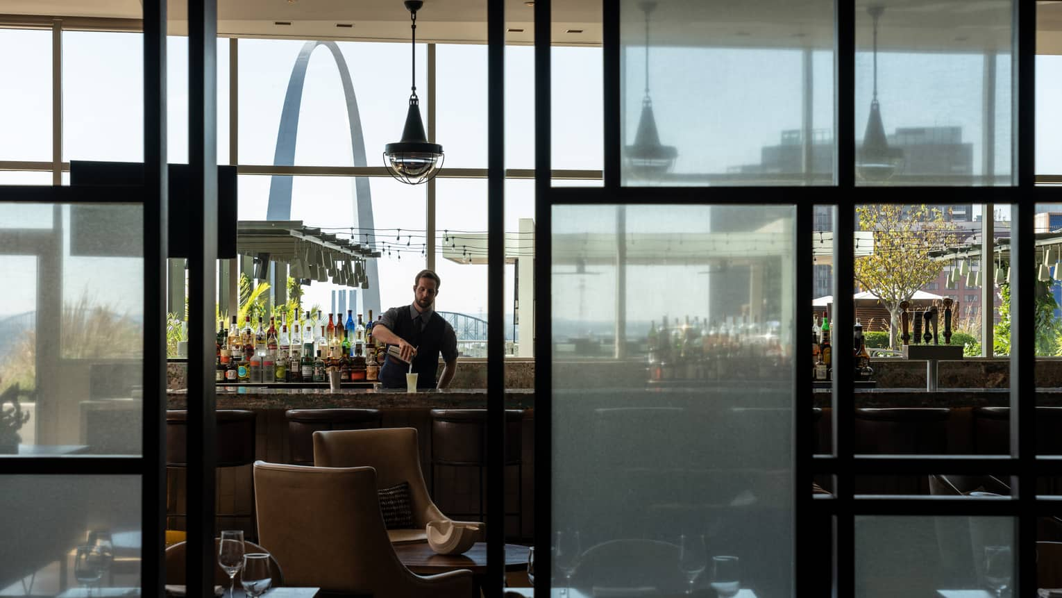 Looking through glass windows at cinderhouse reveals a bartender shaking up a drink at the bar
