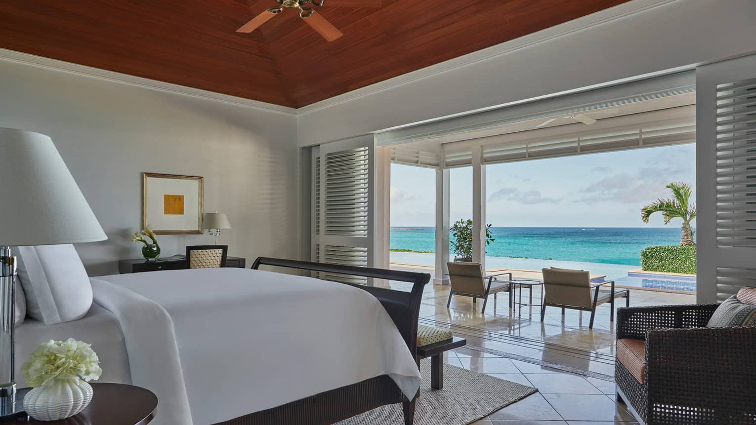 Hotel bed across from open wall to patio overlooking white sand beach, oceanfront