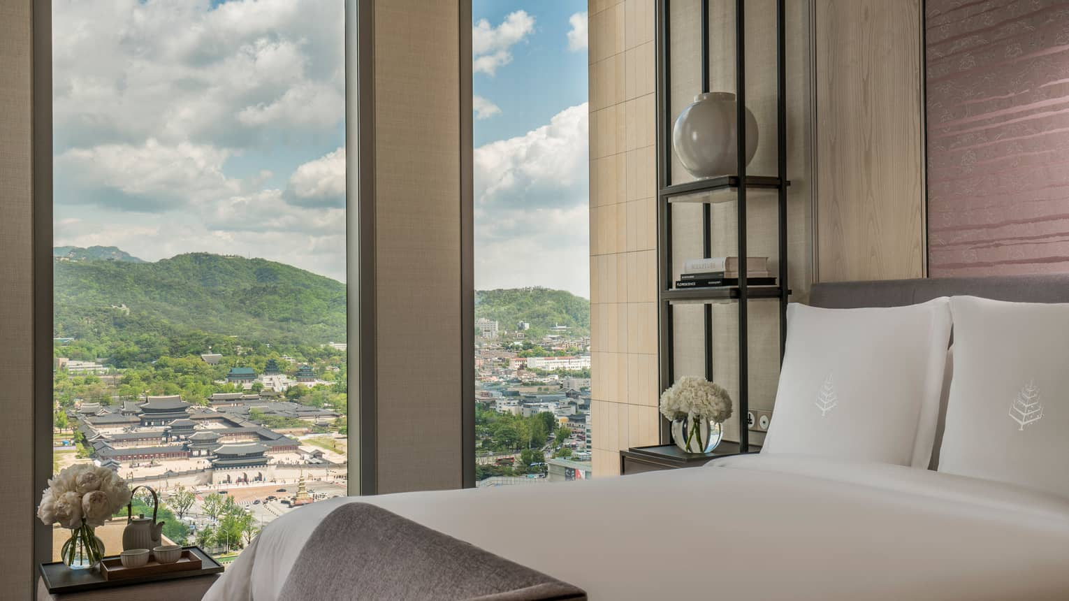 Palace-View Executive Suite bed, chaise at foot, shelf with vases, books beside window overlooking Gyeongbokgung Palace