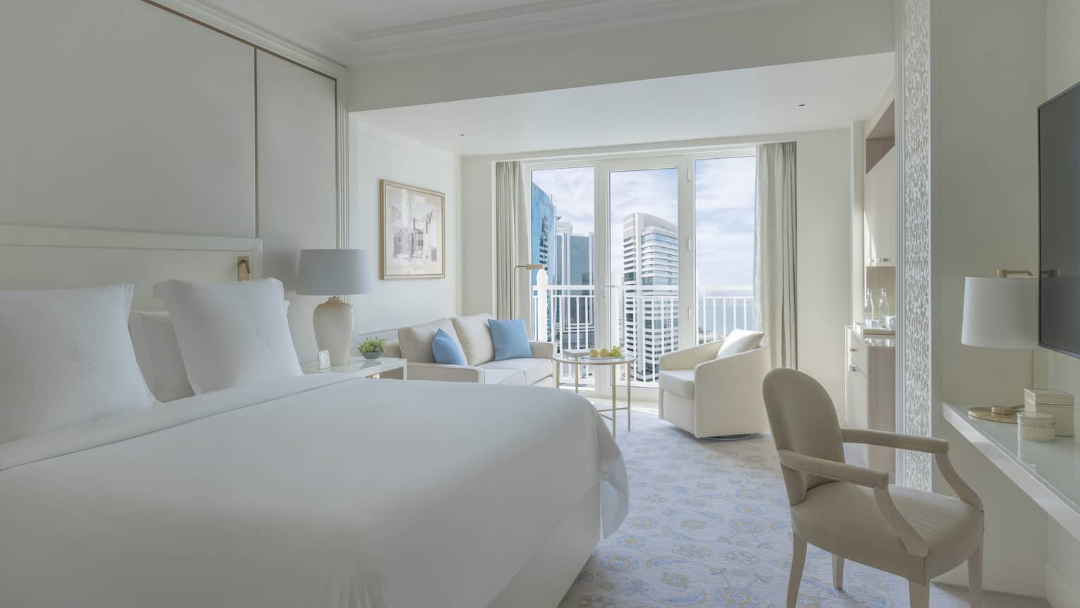 Bedroom with white bed, white walls and a white sofa and arm chair, with balcony offering city view