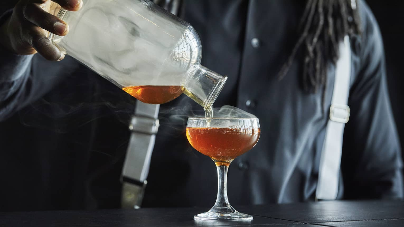 Smoke rolls off the decanter as a Four Seasons staff member pours bourbon into a coupe glass