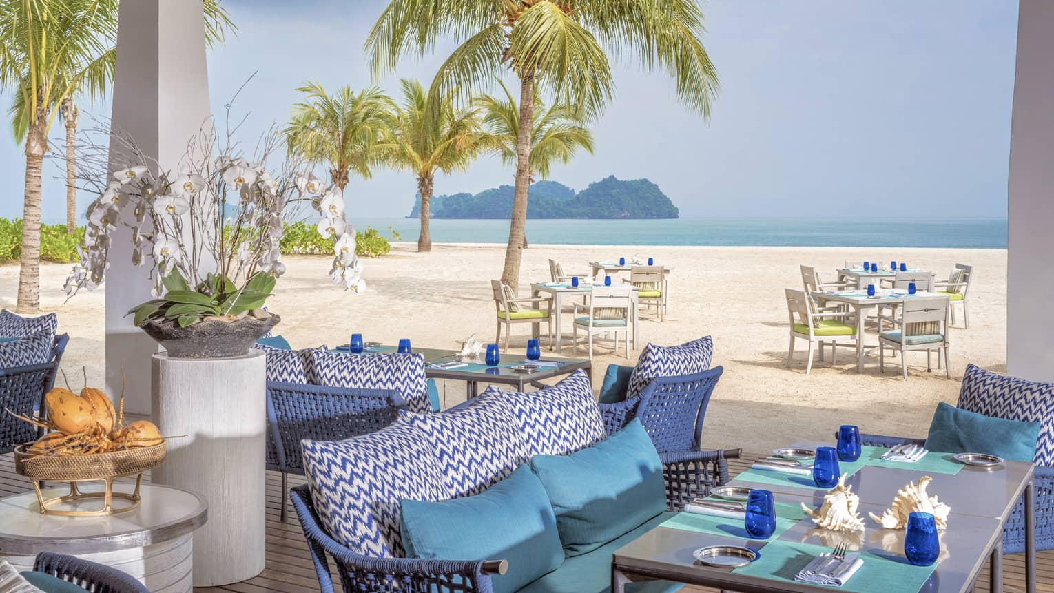 Terrace of ocean-view restaurant, blue cushions on sofa, turquoise place mats and blue glasses on table