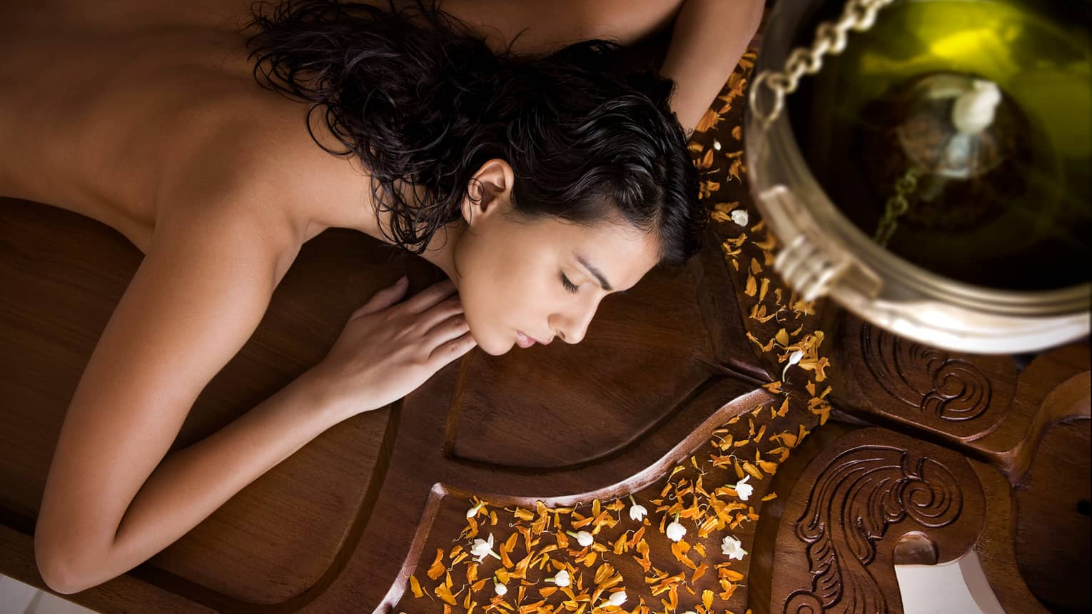 Side view of woman with bare back, shoulders lying on wood Spa table, orange flower petals