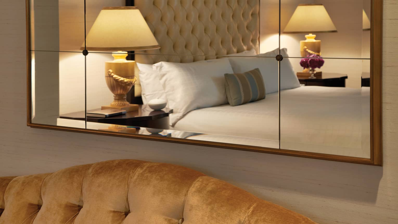 Bed, padded headboard, two lamps seen in reflection of mirror on hotel room wall above sofa