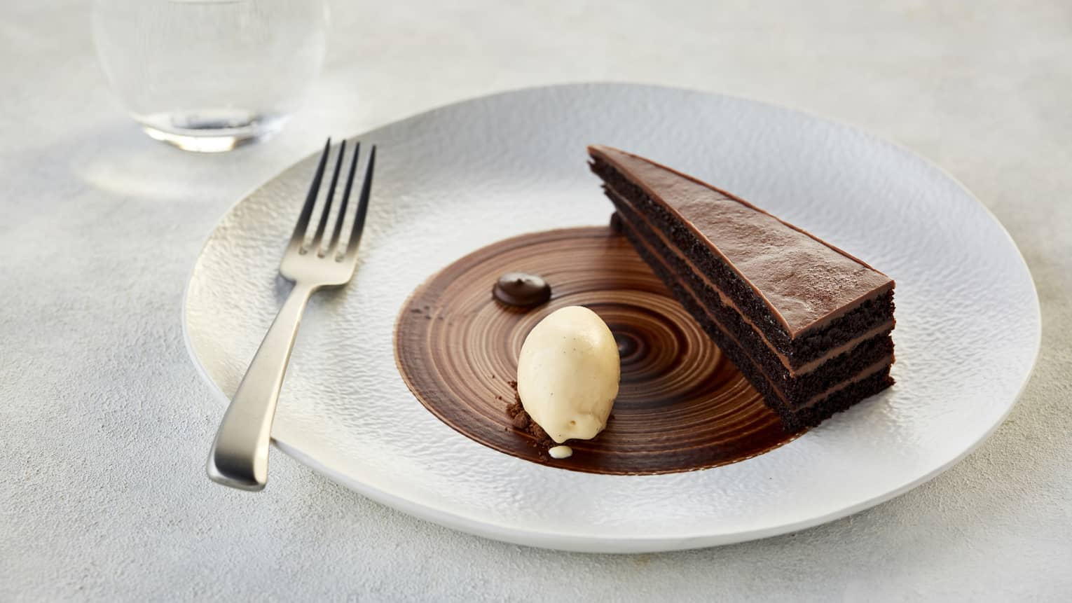 A thin sliced of a layered chocolate ganashe cake garnished with a dallop of cream on a white porcelain plate