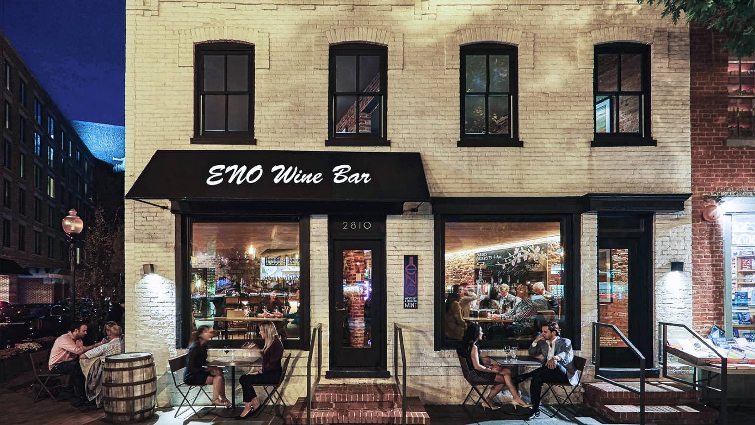 People dine on patio under ENO Wine Bar sign on black awning, white brick building exterior at night