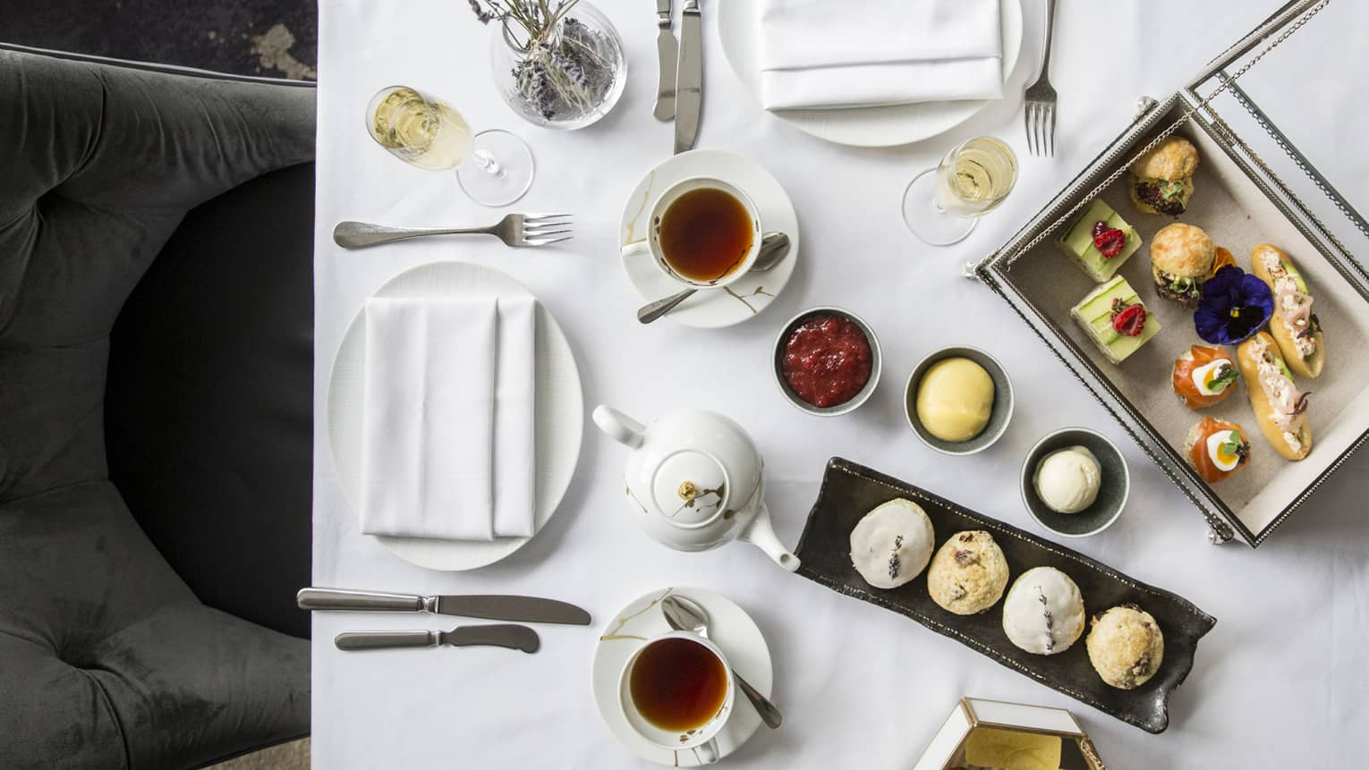 Aerial view of elegant afternoon tea display, complete with finger foods and condiments