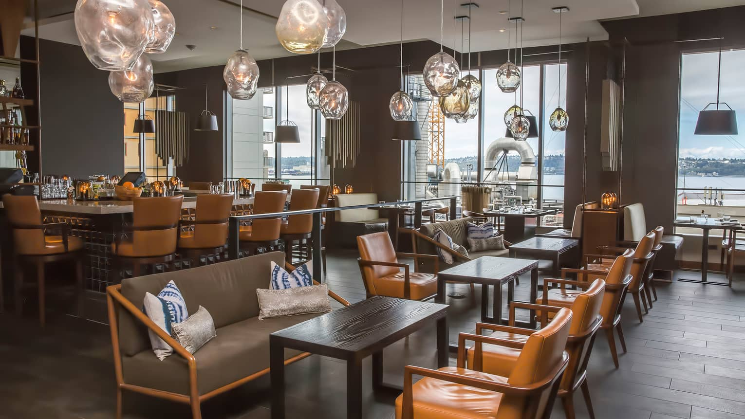 Amber-tinged glass lamps hang above Goldfinch Tavern dining tables, leather chairs