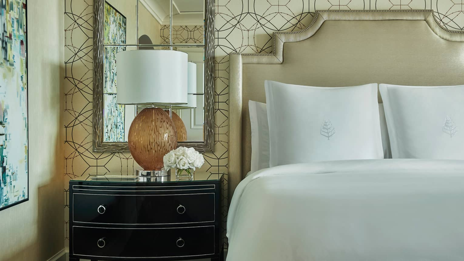 Close-up of Superior Room bed, padded headboard, mirror, lamp on nightstand