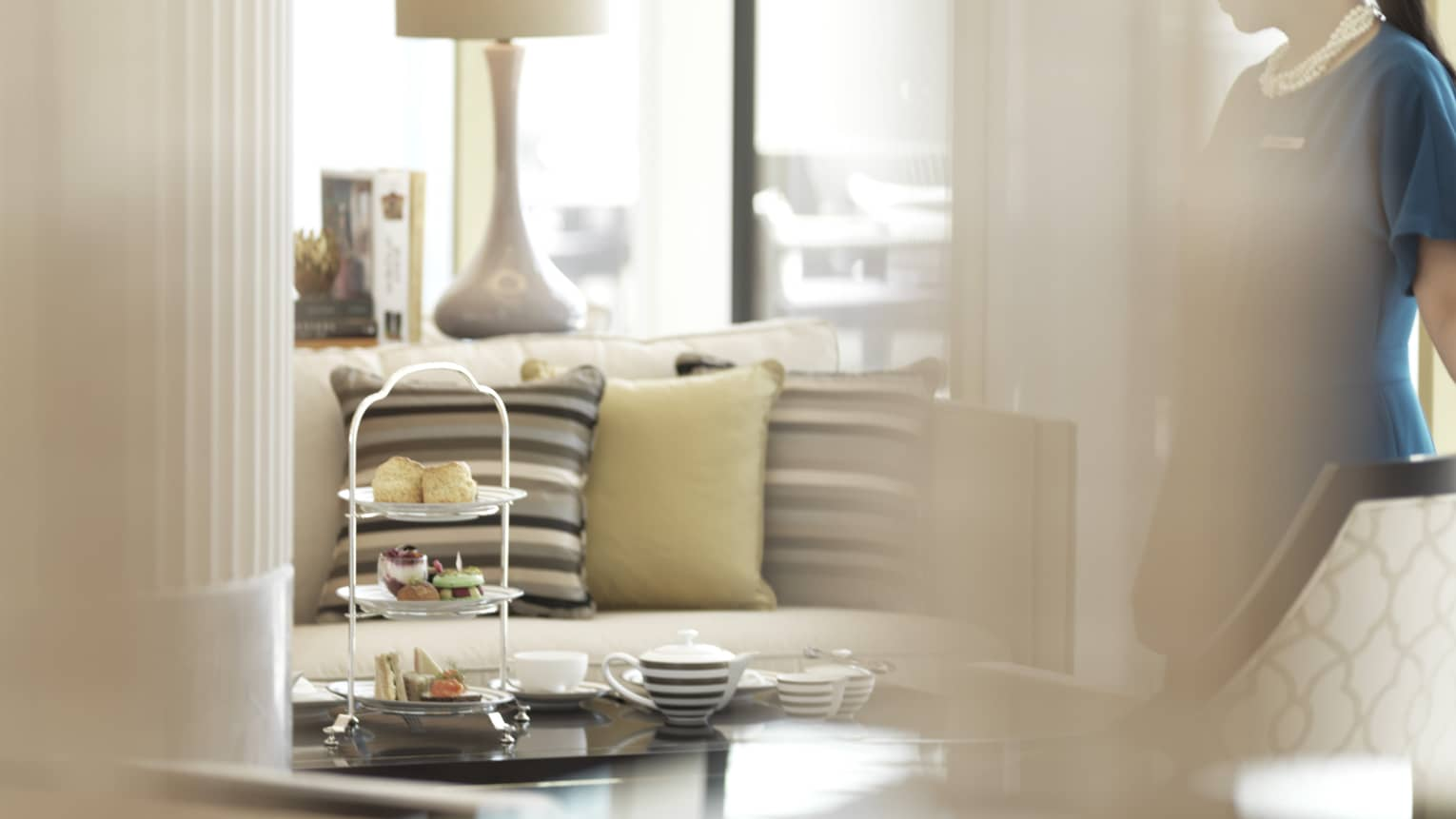 A four seasons staff sets the table for Al Meylas Afternoon Tea in a room with full of the warmth of natural light