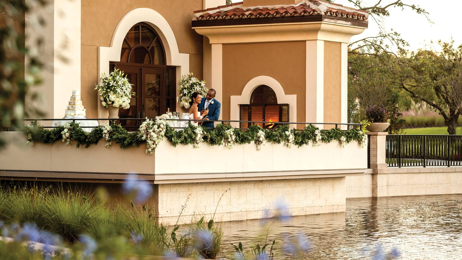 View across water to patio with bride and groom with Champagne, wedding cake, door to event space