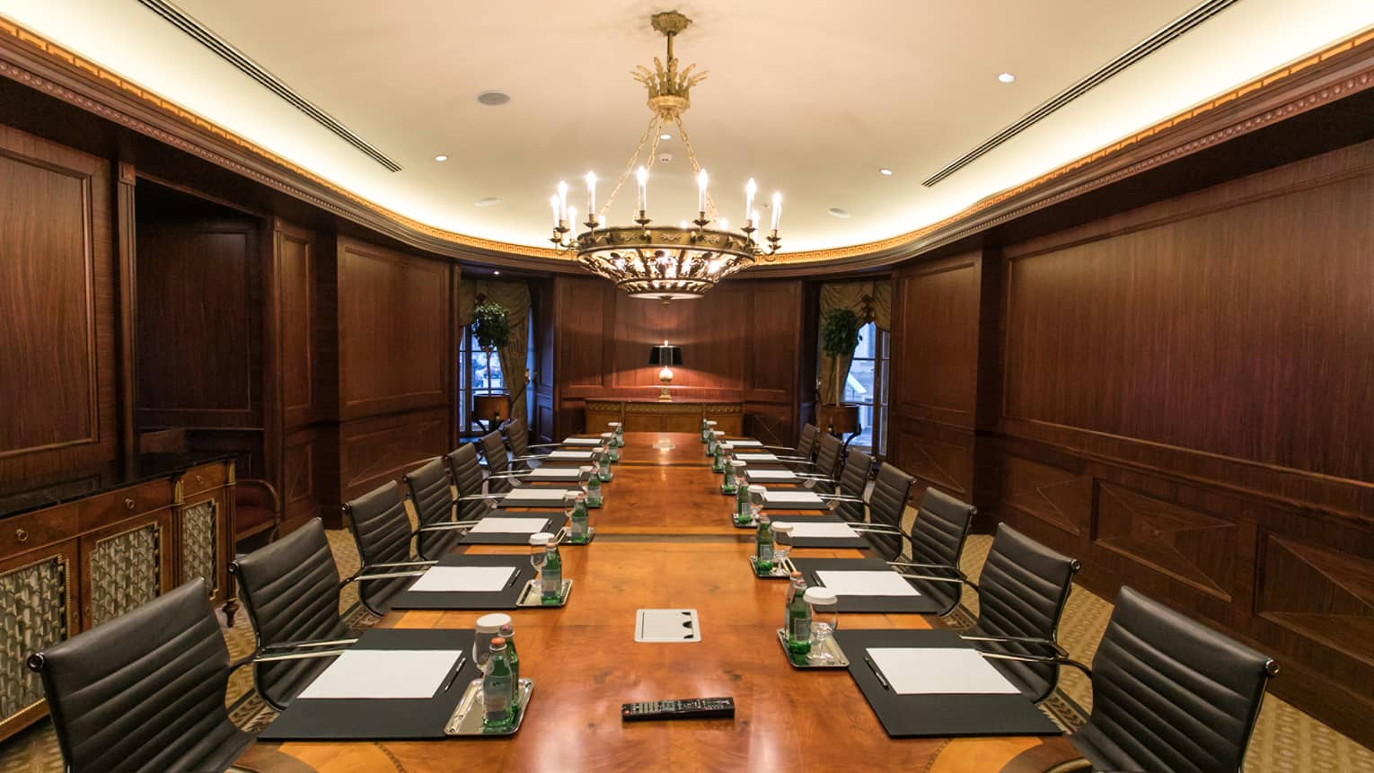 Meeting room with wood panel walls, long boardroom table lined with leather chairs under lamp