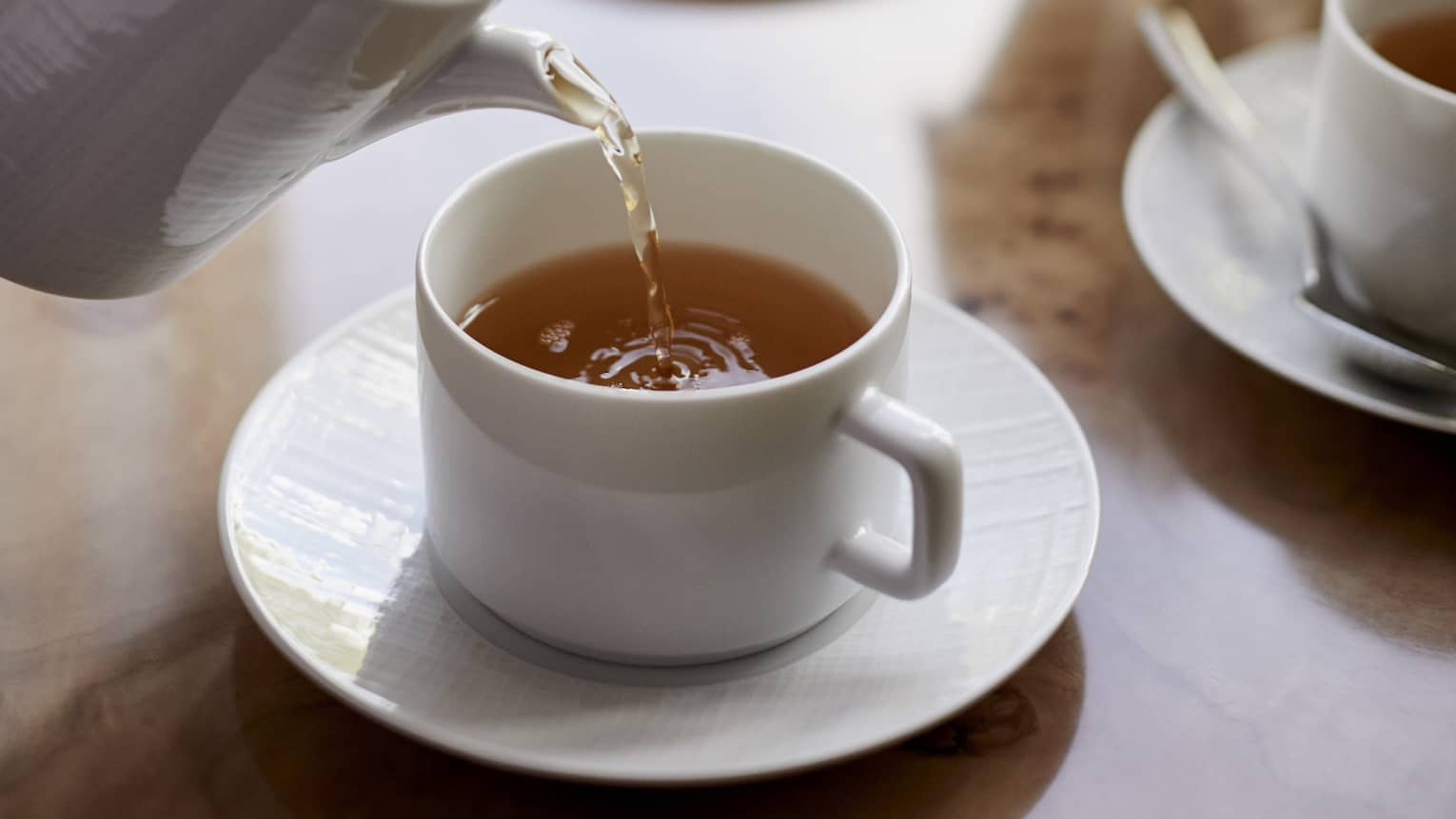 Close-up of tea being poured into white cup