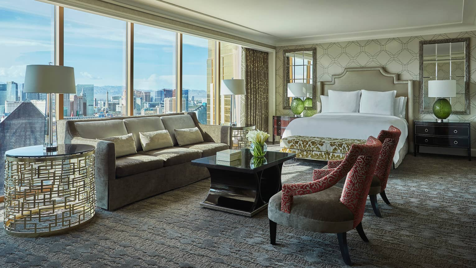 Strip-View Studio grey velvet sofa, gold accent chairs and table, floor-to-ceiling window, city views