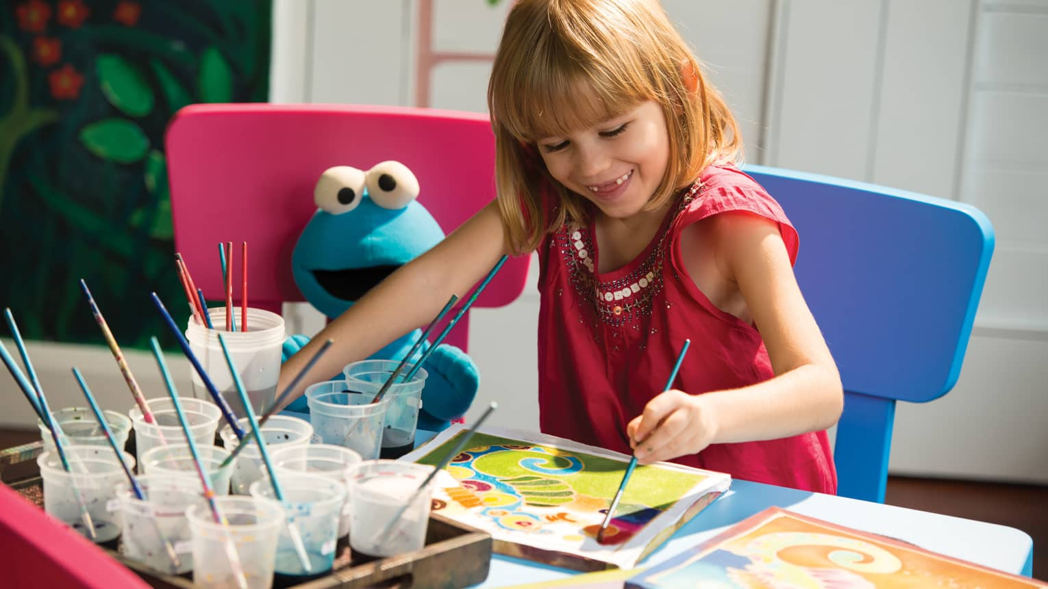 Smiling young girl paints picture at Kids Centre table beside Cookie Monster doll