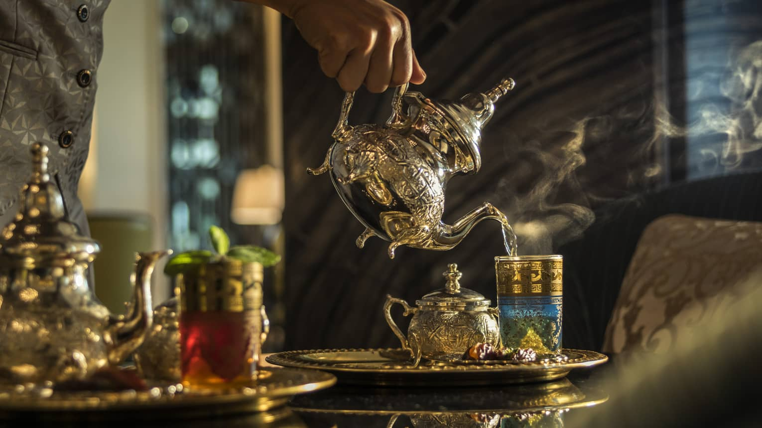 Hand pouring tea from Moroccan-style teapot into glass on tray
