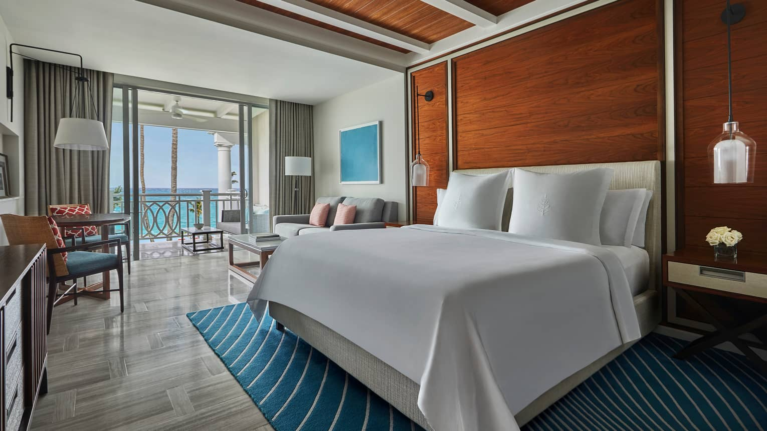 Ocean-View Room bed against wood accent wall on blue area rug, open glass wall to patio with ocean views