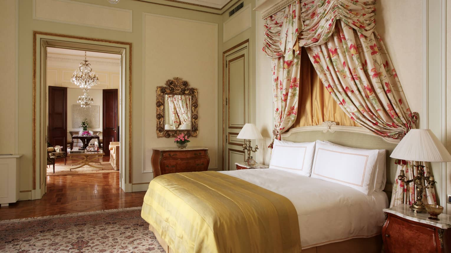 La Mansión Presidential Suite bed with gold blanket, floral drapes above headboard, door to dining room