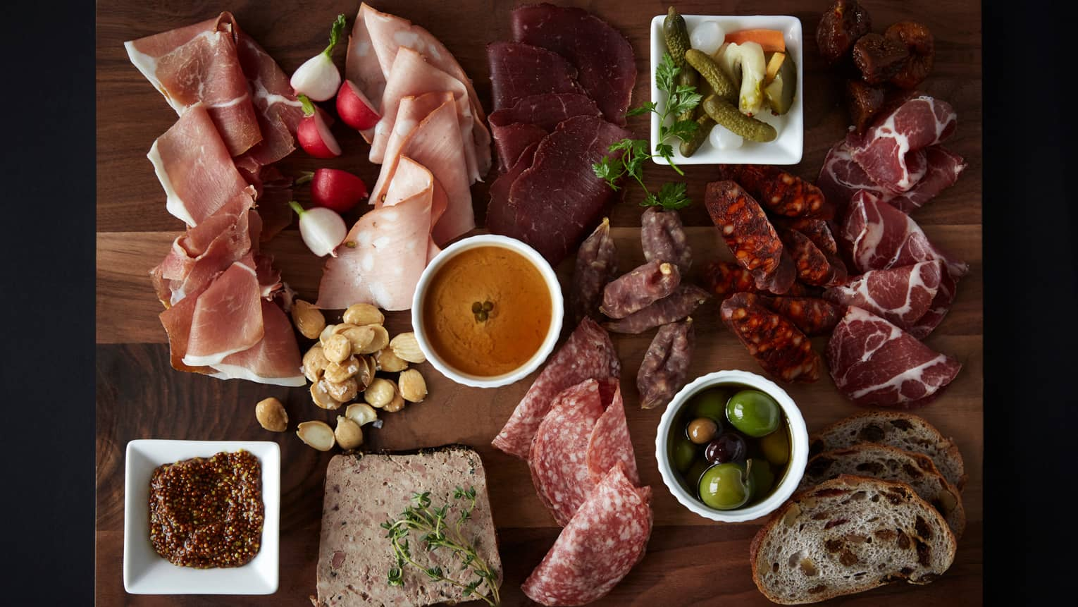 Aerial view of Bourbon Restaurant charcuterie board with cured meats, pickles, olives, pate