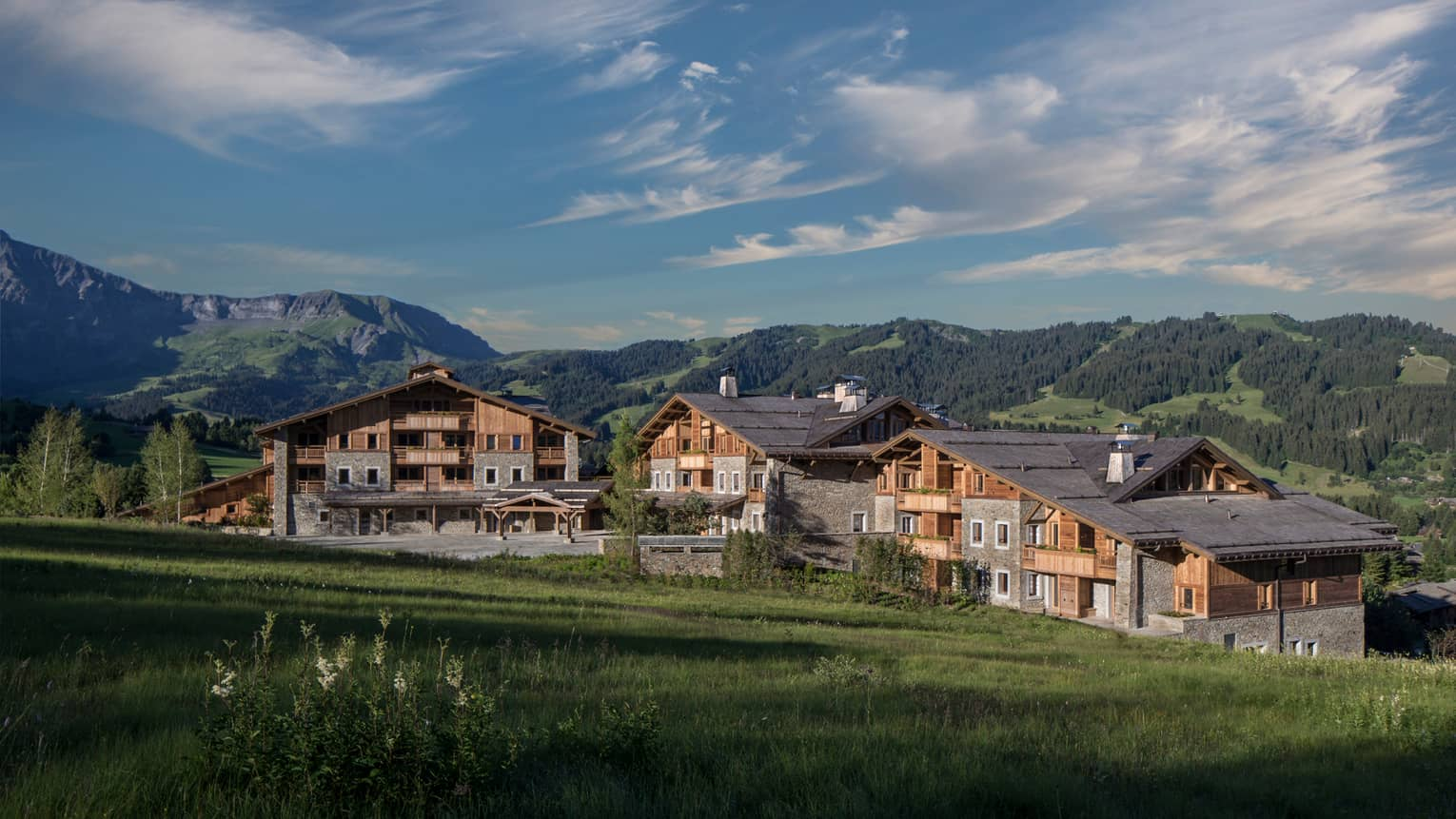 Four Seasons Hotel Megeve rustic ski resort at edge of meadow, mountains