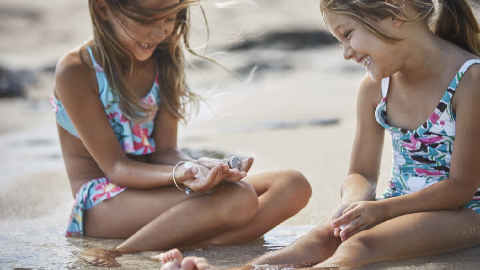 Two smiling young girls in swimsuits sit on sandy beach, look at seashells in hand