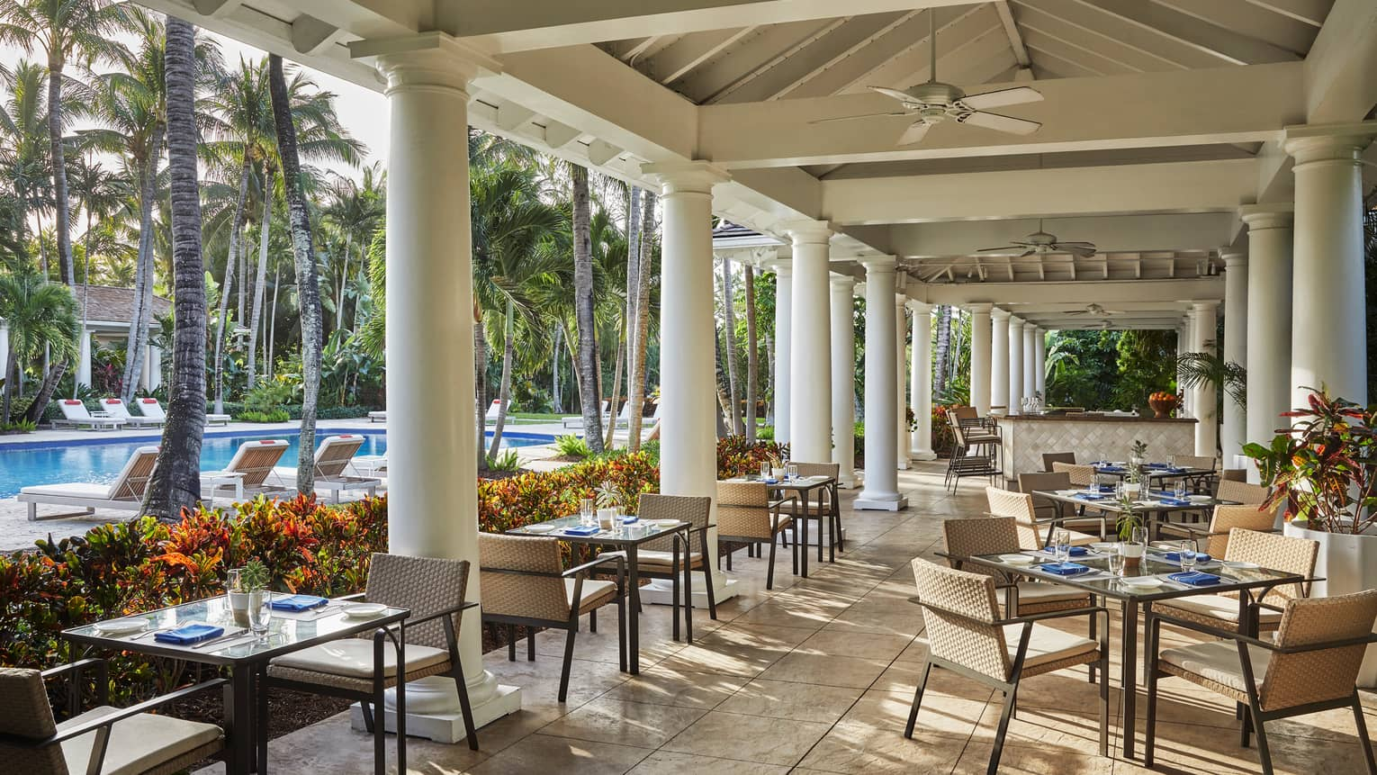 Versailles Terrace restaurant patio, tables under white pillars, ceiling, near swimming pool